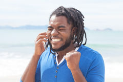 Amerykanina afrykańskiego pochodzenia facet otrzymywa dobre wieści przy telefonem z dreadlocks obraz royalty free
