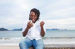 Amerykanina afrykańskiego pochodzenia facet z dreadlocks i białym koszulowym odbiorczym dobre'em wieści obrazy stock