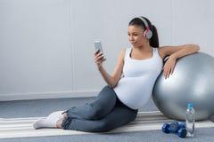 amerykanina afrykańskiego pochodzenia kobieta w ciąży słuchająca muzyka z hełmofonami i smartphone podczas gdy siedzący z dyspono obrazy stock