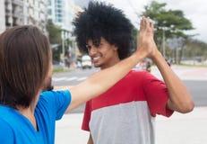Amerykanina afrykańskiego pochodzenia mężczyzna daje wysokości pięć caucasian przyjaciel Zdjęcia Stock