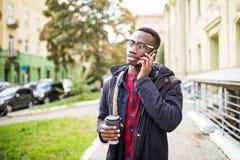 Amerykanina afrykańskiego pochodzenia mężczyzna mówi jego telefon i trzymać kawę na ulicie zdjęcie royalty free