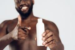 Amerykanina Afrykańskiego Pochodzenia mężczyzna mienia uśmiechnięty aftershave Obraz Royalty Free