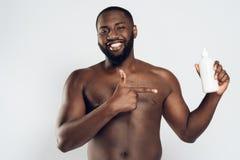 Amerykanina Afrykańskiego Pochodzenia mężczyzna mienia uśmiechnięty aftershave Obrazy Royalty Free