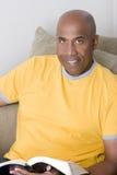 Amerykanina Afrykańskiego Pochodzenia mężczyzna obsiadanie na czytaniu i kanapie obrazy stock