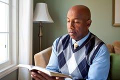 Amerykanina Afrykańskiego Pochodzenia mężczyzna obsiadanie na kanapy czytaniu Zdjęcia Stock