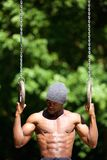 Amerykanina afrykańskiego pochodzenia mężczyzna treningu rutyna na gimnastyczka pierścionkach Zdjęcie Stock