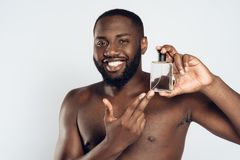 Amerykanina Afrykańskiego Pochodzenia mężczyzna używa aftershave płukankę Obrazy Royalty Free