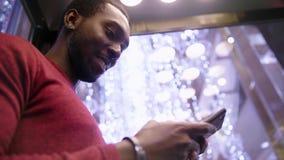 Amerykanina Afrykańskiego Pochodzenia mężczyzna używa biznes app na mądrze telefonie zbiory wideo