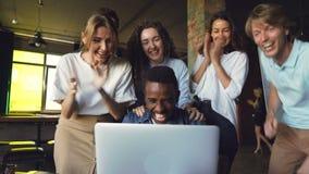 Amerykanina Afrykańskiego Pochodzenia mężczyzna urzędnik excited o dobrze wieści, jest przyglądającym laptopu ekranem i śmiający  zbiory