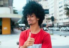 Amerykanina afrykańskiego pochodzenia mężczyzna z typowym afro włosianym pokazuje kciukiem up Fotografia Royalty Free