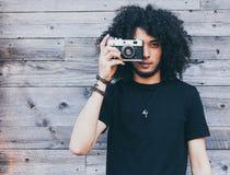 Amerykanina afrykańskiego pochodzenia mężczyzna z typowym afro włosy bierze obrazek rocznik kamera przeciw tłu stare deski Zdjęcia Stock