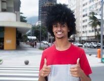 Amerykanina afrykańskiego pochodzenia mężczyzna z typowym afro włosy pokazuje oba kciuki Obrazy Royalty Free