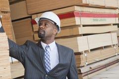 Amerykanina Afrykańskiego Pochodzenia męski inżynier sprawdza drewniane deski Fotografia Stock