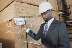 Amerykanina Afrykańskiego Pochodzenia męski kontrahent używa pastylka peceta podczas gdy sprawdzać drewniane deski Zdjęcie Stock