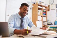 Amerykanina Afrykańskiego Pochodzenia męski nauczyciel pracuje przy jego biurkiem Obraz Royalty Free