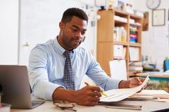 Amerykanina Afrykańskiego Pochodzenia męski nauczyciel pracuje przy jego biurkiem Obrazy Stock