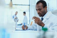 Amerykanina afrykańskiego pochodzenia naukowiec trzyma próbnej tubki i egzamininuje w białym żakiecie z odczynnikiem obrazy royalty free
