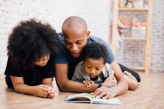 Amerykanina Afrykańskiego Pochodzenia ojciec czyta bajki bajki opowieść dla dzieciaków w domu fotografia royalty free