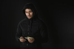 Amerykanina afrykańskiego pochodzenia rabuś w zoodie mienia pieniądze odizolowywającym na czerni Obraz Stock