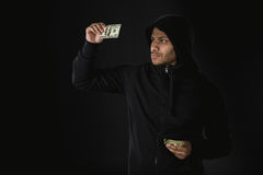 Amerykanina afrykańskiego pochodzenia rabuś w zoodie mienia pieniądze odizolowywającym na czerni Obrazy Royalty Free
