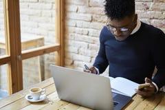 Amerykanina afrykańskiego pochodzenia uczeń szkoła biznesu w ciemnego puloweru i białego koszulowego writing znacząco notatkach w Zdjęcia Royalty Free
