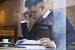 Amerykanina afrykańskiego pochodzenia uczeń szkoła biznesu w ciemnym pulowerze i biała koszulowa odpowiedź na dzwonić od operator Obrazy Royalty Free