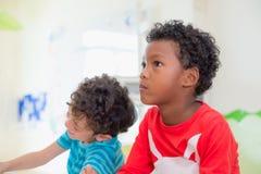 Amerykanina Afrykańskiego Pochodzenia pochodzenia etnicznego dzieciak z markotnym emoci obsiadaniem w cla Zdjęcie Stock