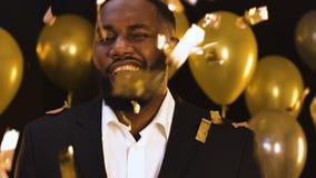 Amerykanina mężczyzny pozycja pod spada confetti i mrugać kamera, przyjęcie zdjęcie wideo