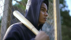 Amerykanina nastolatka mienia kij bejsbolowy, gang młodocianych przestępców w getcie, zbliżenie zdjęcia stock