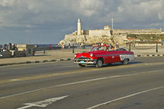 Amerykański czerwony odwracalny samochodowy jeżdżenie za Castillo Del Morro przez Hawańskiego kanał, Kuba Obrazy Royalty Free
