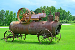 Ames Steam Engine Iron Works A.B. Farquhar. Old antique Ames Iron Works Steam Engine sitting on display in grassy field with storm clouds and trees in the Stock Photos
