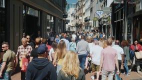 Amesterdam,荷兰, 2018年5月:有许多的一条活泼的街道商店、咖啡馆和精品店 游人人群去 影视素材
