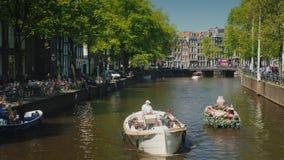 Amesterdam,荷兰, 2018年5月:用花装饰的小船沿运河漂浮在阿姆斯特丹 在a的旅游业 影视素材