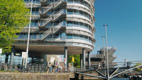 Amesterdam,荷兰, 2018年5月:阿姆斯特丹现代建筑学-在运河的一座桥梁和巨大的停车处为 影视素材