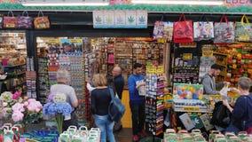 Amesterdam, die Niederlande, im Mai 2018: Besucher wählen Blumen und Andenken am berühmten Blumenmarkt in Amsterdam stock video footage