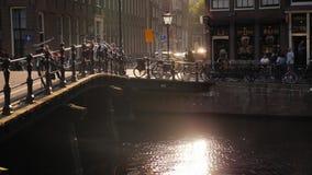 Amesterdam Nederländerna, Maj 2018: Härlig solnedgång i staden Sol- ilsken blick i vattnet, cyklar parkerade av kanalen stock video
