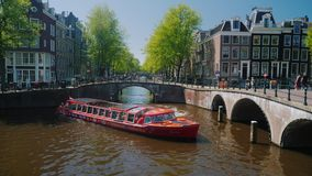 Amesterdam, Netherlands, May 2018: A large red boat with tourists sails along the canal in Amsterdam stock footage