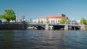 Amesterdam, Países Bajos, mayo de 2018: Travesía a través de los canales de Amsterdam Nade más allá del edificio de la ópera y metrajes