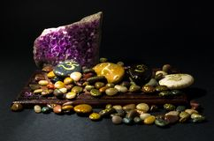 Amethyst crystal and colorful stones over a wooden board Royalty Free Stock Photography