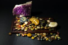 Amethyst crystal and colorful stones painted with Om symbol Royalty Free Stock Photo