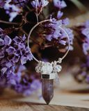 Amethyst Crystal Earrings. Hoop with staticec flower in background on point polished stock images