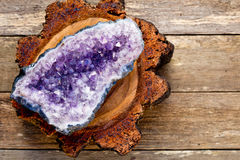 Amethyst crystal geode on cross section of timber log with woode Royalty Free Stock Images