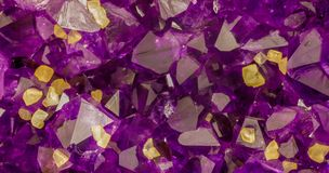 Amethyst crystals with yellow calcite cubes background image. High magnification macro photo of amethyst crystals with yellow calcite cubes. Background image royalty free stock images