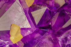 Amethyst crystals with yellow calcite cubes macro photo. High magnification macro photo of amethyst crystals with yellow calcite cubes. Background image royalty free stock image