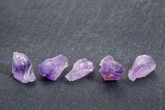 Amethyst gemstones on slate stone. A row of rough amethysts gemstones on gray slate stone background Stock Images