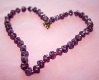 Amethyst Heart. Purple tones of amethyst necklace are complimented by pink background.  Necklace is displayed in heart shape Royalty Free Stock Image