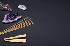 Amethyst and quartz crystal stones, palo santo wood, Aromatic sticks and decorative bottle on black background. Composition of esoteric objects used for healing royalty free stock photography