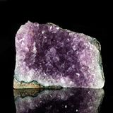 Amethyst rock on black reflective background. Birthstone. Mineralogy and gemology royalty free stock image