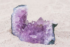 Amethyst rock on sand background Stock Images
