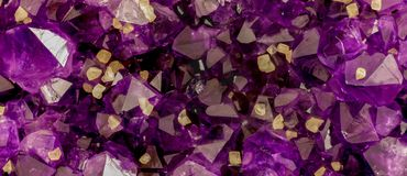Amethyst stone crystals background image. Yellow ones are calcite crystals royalty free stock photography